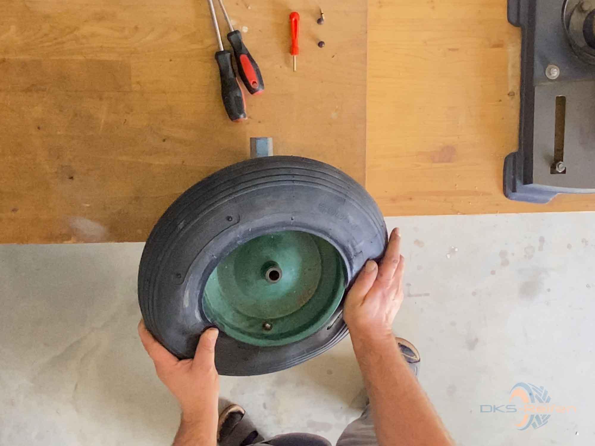 Schubkarrenrad wechseln: Reifen über die Felge drücken